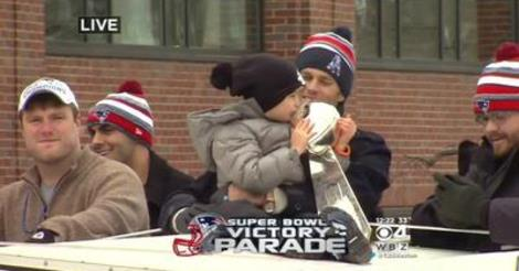Tom Brady's son kissing the Super Bowl trophy during the parade